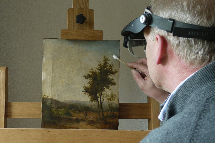 Een man restaureert een schilderij